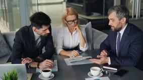 Gente di affari che analizza i documenti finanziari che lavorano in caffè durante l'intervallo di pranzo stock footage