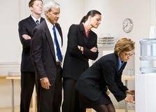 Gente di affari che attende girata al dispositivo di raffreddamento di acqua Immagini Stock