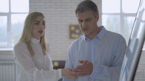 Gente di affari che confronta le idee le idee su una lavagna in un grande ufficio corporativo Lavoratori attraenti che sviluppano stock footage