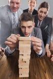 Gente di affari che costruisce torre di legno immagini stock