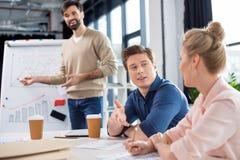 Gente di affari che discute i grafici e le statistiche sulla piccola riunione dell'ufficio Immagini Stock