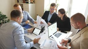 Gente di affari che discute i grafici ed i grafici di reddito nel corso della riunione del gruppo nell'ufficio moderno Giovani co archivi video