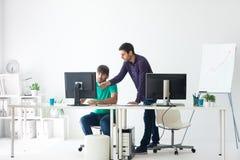 Gente di affari che discute le idee alla riunione facendo uso del computer Fotografia Stock