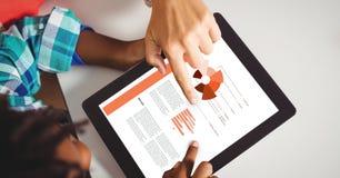 Gente di affari che discute sopra i grafici sulla compressa digitale immagine stock