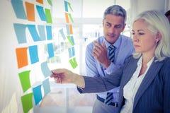 Gente di affari che esamina Post-it sulla parete Immagine Stock