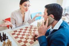 Gente di affari che gioca scacchi con l'uomo sul telefono immagine stock