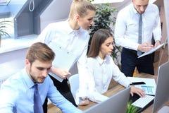 Gente di affari che lavora ai loro desktop computer allo spazio ufficio moderno immagini stock