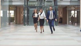 Gente di affari che passa l'ingresso di un edificio per uffici Movimento lento archivi video
