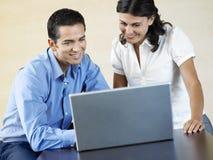 Gente di affari che per mezzo del computer portatile allo scrittorio immagine stock libera da diritti
