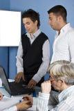Gente di affari che per mezzo di un computer portatile Immagini Stock Libere da Diritti