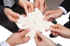 Gente di affari che ripara i pezzi del puzzle Immagine Stock