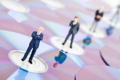 Gente di affari che si leva in piedi sui Cd del calcolatore Fotografie Stock