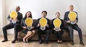 Gente di affari che si siede insieme alle icone della lampadina Fotografie Stock