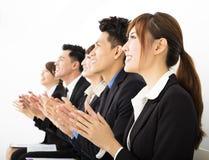 Gente di affari che si siede in una fila e che applaude Fotografia Stock
