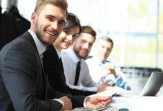 Gente di affari che si siede in una fila ed in un funzionamento, fuoco sul giovane Fotografia Stock
