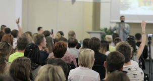 Gente di affari che solleva là mano su ad una conferenza per rispondere ad una domanda 4k video d archivio