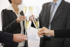 Gente di affari che solleva pane tostato con champagne Fotografie Stock