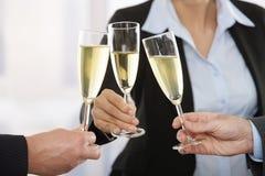 Gente di affari che solleva pane tostato con champagne Fotografia Stock