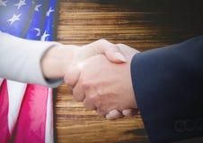 Gente di affari che stringe le loro mani contro la bandiera americana Fotografie Stock