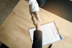 Gente di affari che stringe le mani con stipulare un contratto nel offi immagini stock libere da diritti