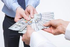Gente di affari che tiene i dollari Immagine Stock