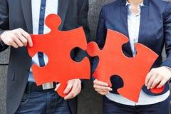 Gente di affari che tiene puzzle rosso Fotografia Stock Libera da Diritti