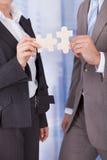 Gente di affari che unisce i pezzi del puzzle in ufficio Fotografia Stock