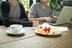 Gente di affari del lavoro di gruppo con il computer portatile con frutta fresca Fotografia Stock