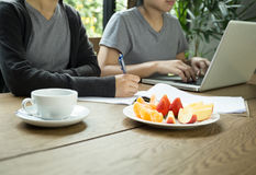 Gente di affari del lavoro di gruppo con il computer portatile con frutta fresca Immagine Stock