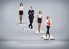 Gente di affari del supporto sulle scale di puzzle Fotografia Stock Libera da Diritti