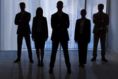 Gente di affari della siluetta che sta nell'ufficio Fotografie Stock Libere da Diritti