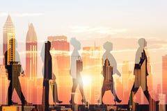 Gente di affari della siluetta e costruzioni moderne durante il tramonto fotografia stock libera da diritti