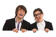 Gente di affari di risata dietro il cartello. fotografia stock