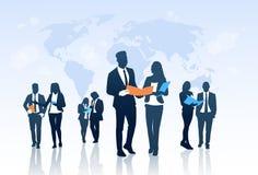 Gente di affari di Team Crowd Silhouette Businesspeople Group delle cartelle documenti della tenuta sopra la mappa di mondo royalty illustrazione gratis