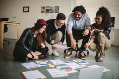 Gente di affari discutendo i piani sedendosi sul pavimento con le carte immagine stock