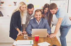 Gente di affari felice del gruppo insieme al computer portatile in ufficio Immagini Stock Libere da Diritti