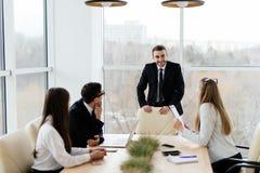 Gente di affari in formalwear che discute con il capo qualcosa mentre sedendosi insieme alla tavola Immagini Stock Libere da Diritti