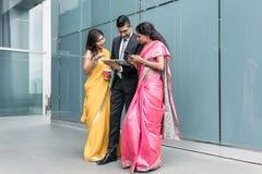 Gente di affari indiana che per mezzo dei dispositivi alta tecnologia durante la pausa Fotografia Stock