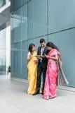 Gente di affari indiana che per mezzo dei dispositivi alta tecnologia durante la pausa Immagini Stock