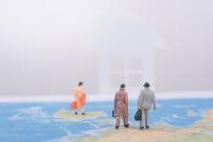 Gente di affari miniatura di viaggio che va a casa sulla mappa di mondo Immagine Stock Libera da Diritti