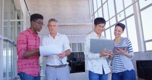 gente di affari Multi-etnica che discute sopra il documento ed il computer portatile nell'ufficio moderno 4k video d archivio