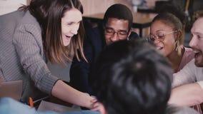 Gente di affari multietnica emozionante felice che si prende per mano celebrando vittoria e successo corporativi del gruppo alla  archivi video