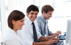 Gente di affari positiva che lavora ai calcolatori Immagini Stock