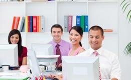 Gente di affari positiva che lavora ai calcolatori Fotografia Stock Libera da Diritti