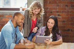 Gente di affari sorridente che discute sopra la compressa nell'ufficio creativo immagini stock