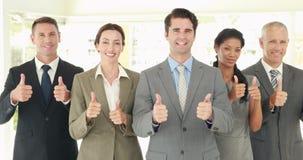 Gente di affari sorridente che esamina macchina fotografica che gesturing i pollici su stock footage