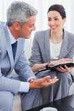 Gente di affari sorridente che lavora insieme e che parla sul sofà Immagini Stock