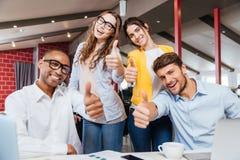 Gente di affari sorridente che mostra i pollici su che funzionano nell'ufficio Immagini Stock Libere da Diritti