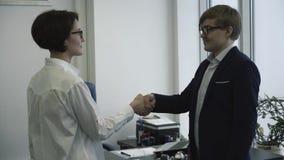 Gente di affari sorridente che stringe le mani nel loro ufficio Riunione d'affari video d archivio