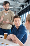 Gente di affari sorridente che stringe le mani sulla piccola riunione dell'ufficio Fotografia Stock